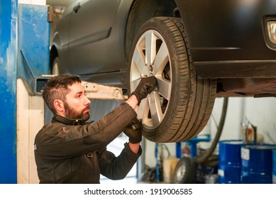 Mechanic performs tire change on the car in the workshop