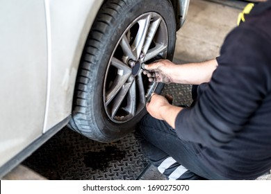 Mechanic with pneumatic wrench unscrews the wheel.Mechanic repairing a car wheel.Male mechanic at a car garage fixing a wheel