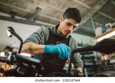 Mechanic polishing and cleaning a motorcycle in a workshop
