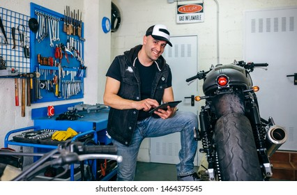 Mechanic posing checking custom motorcycle with tablet in his workshop