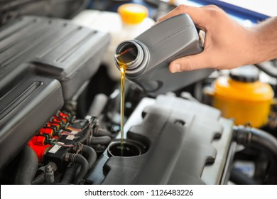 Mechanic pouring oil into car engine, closeup