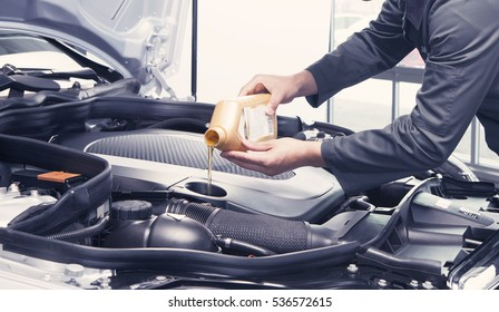 Mechanic pouring oil into car at the repair garage