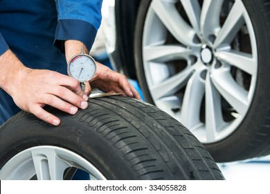 Mechanic, pressing a gauge into a tire tread to measure its depth for vehicle and road safety