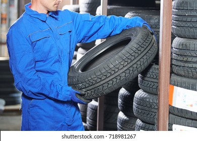 mechanic pulls tire from the tyre store warehouse