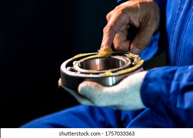 Mechanic is putting lubricant grease into ball bearing isolated on black background, Technician Industrial Concept