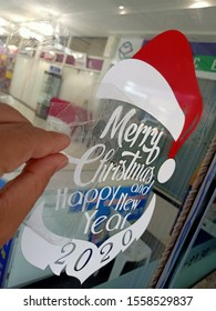 The mechanic is putting sticker Marry Christmas and Happy New Year 2020 on the glass.