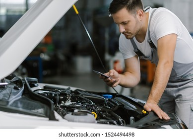 Mechanic reading a text message on smart phone in a workshop