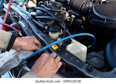 A mechanic is refilling coolant to air condition of a car