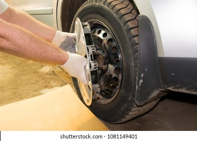 A mechanic removing the hubcap from a car wheel. Tire fitting.