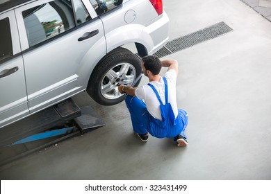 Mechanic removing a tire from a car with an air wrench