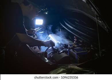 Mechanic  repair the car at night . Check water in Car radiator ,car broken down