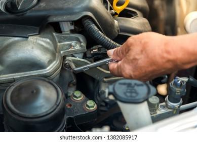 The mechanic is repairing the car engine.repair engine