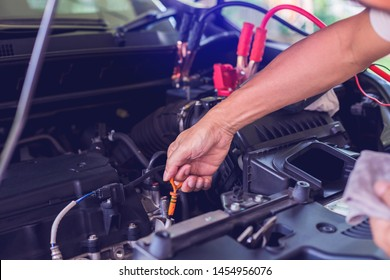 Mechanic repairing car with open hood,Side view of mechanic checking level motor oil in a car with open hood. blurry voltmeter for check voltage in battery. Repair service. Selective focus.