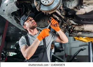 mechanic repairing car without wheel in workshop