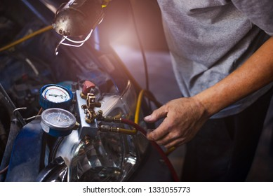 Mechanic repairing a car,Check car air conditioning system refrigerant recharge,Auto mechanic Worker hands holding and point to monitor to check and fixed car air conditioner system in car service.