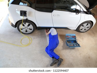 Mechanic repairing an electric driven car in garage