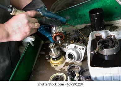 Mechanic repairing electric generator, repair of starter