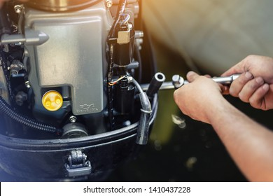 mechanic repairing inflatable motorboat engine at boat garage. Ship engine seasonal service and maintenance. Vessel motor with open cover