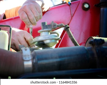 Mechanic repairing large red tractor.