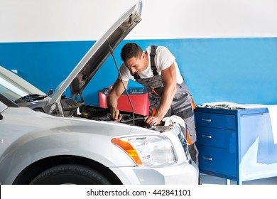 Mechanic repairing a lifted car at garage
