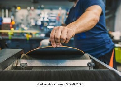 Mechanic repairing Snowboard. Hard work is the key to success. Specialist in Snowboard, repairing a Snowboard in his workshop. Winter shop worker doing base repair