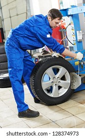 mechanic repairman balancing automobile car wheel on balancer