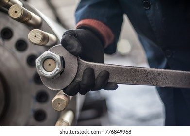 Mechanic repairman at the factory screws big bolt with large and heavy wrench key, holding it with both hands