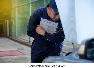 Mechanic repairman inspecting car, Maintaining car records. Auto technician checking car engine holding paperwork for checkup inspector after fixing. Auto service concept. mechanic check list on car.