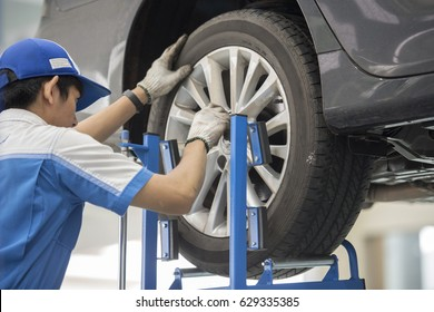 mechanic repairman making tyre fitting screwing out a wheel nipple