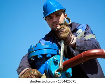 The mechanic - the repairman tightens bolts on a flanged connection of pipeline armature
