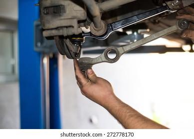 Mechanic repairs the car.