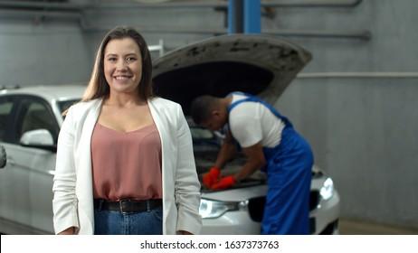 Mechanic repairs a car, woman smiles at the camera