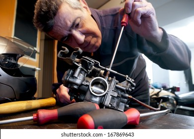 Mechanic repairs the carburetor of his motorcycle