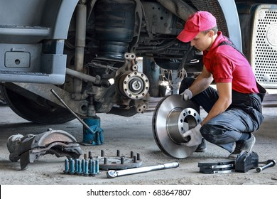 A mechanic repairs a truck. Replace brake disc and pads