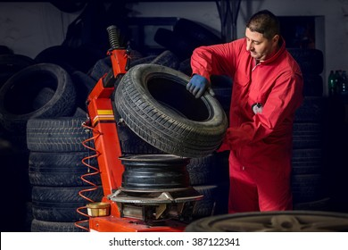 mechanic replace tyre on wheel in workshop