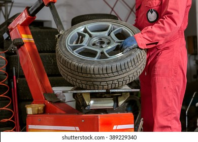 mechanic replace tyre on wheel in workshop