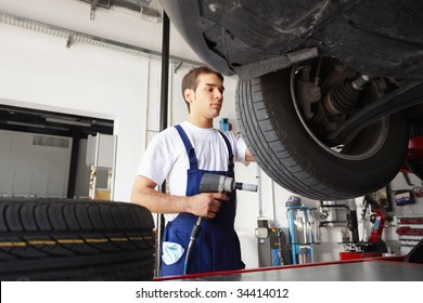 mechanic replacing car tyre in auto repair shop. Low angle view
