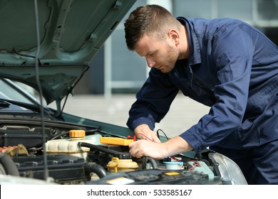 Mechanic with scan tool diagnosing car in open hood. Closeup