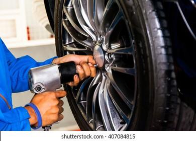 mechanic screwing or unscrewing car wheel at car service garage