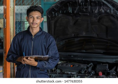 A mechanic service car in garage is paper check a list cars.