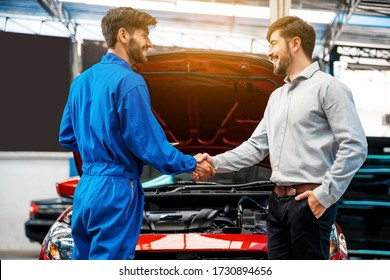 The mechanic shaking hands with customer after finish checking the opened hood red car. Focus on happy mechanic and satisfied customer. Auto car repair service center. Professional service.