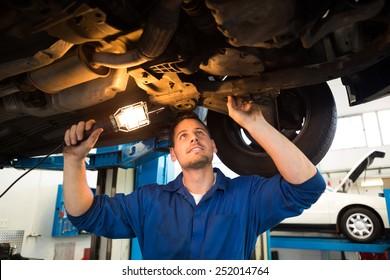 Mechanic shining torch under car at the repair garage