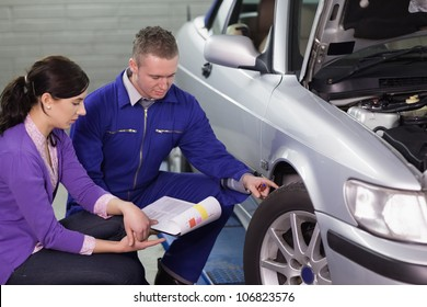 Mechanic showing the car wheel to a woman in a garage