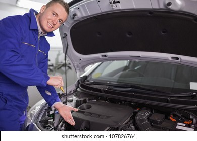 Mechanic showing an engine with his hand in a garage