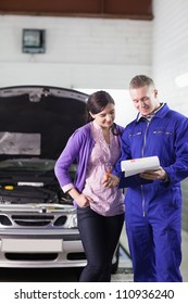 Mechanic showing a paper in a clipboard to a client in a garage