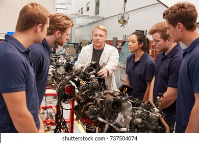 Mechanic showing parts of an engine to apprentices, close up
