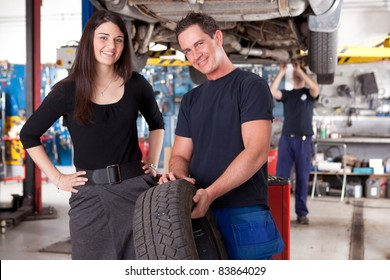 A mechanic showing a tire to a happy female customer