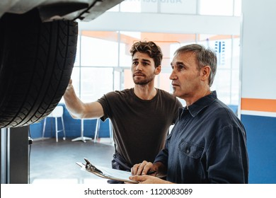 Mechanic showing the wheel of car to colleague making notes in clipboard. Auto service professionals examining the car and making notes.