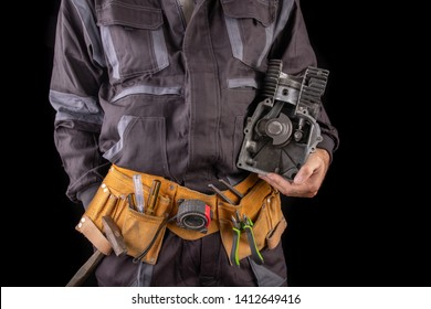 Mechanic with a small combustion engine in hand. A specialist in the repair of internal combustion engines. Dark background.