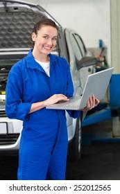 Mechanic smiling at the camera holding laptop at the repair garage